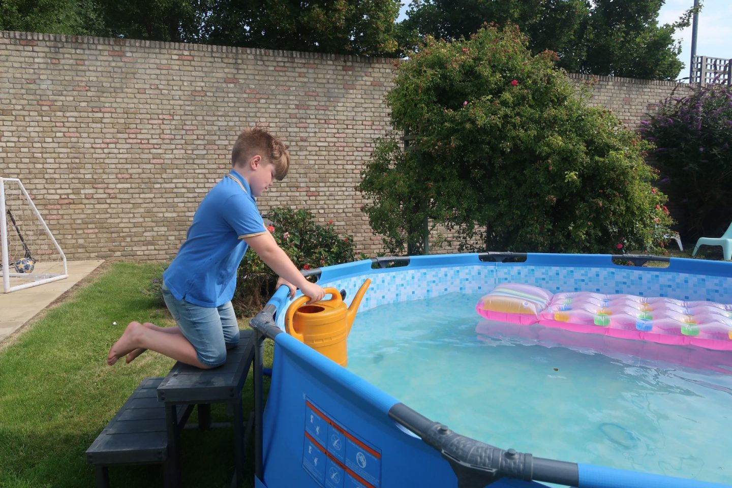 boy watering the garden with paddling pool water